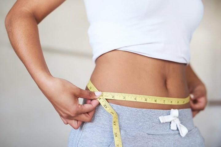 Mulher que mede a cintura com uma fita métrica