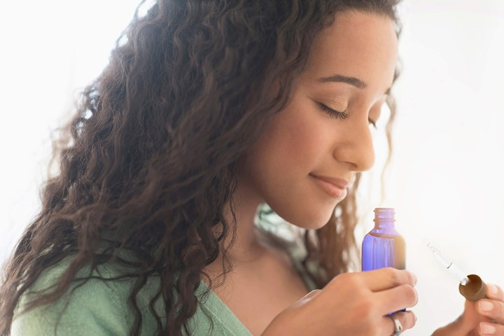 Woman smelling essential oil out of a blue bottle